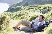 Man Relaxing On Cliffside Path