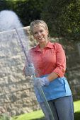 Portrait of a middle aged woman spraying pesticides at garden
