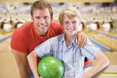 foto of bowling ball  - Man and son smiling at bowling alley - JPG
