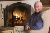 Man Sitting In Living Room By Fireplace Smiling
