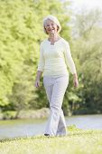 Woman Walking Outdoors At Park By Lake Smiling