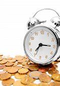 Alarm clock on gold coins.