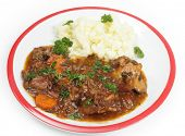 Um prato de guisado de rabo de boi old-fashioned, servido com purê de batata e guarnecido com salsa inglesa