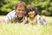 Father And Daughter Lying Outdoors With Flowers Smiling