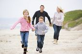 Families Running At Beach Holding Hands Smiling