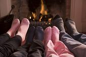 Families Of Feet Warming At A Fireplace