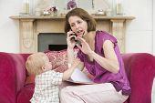 Madre con el teléfono en la sala de estar con el bebé bostezando