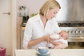 Mother Feeding Baby In Kitchen With Coffee