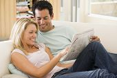 Couples In Living Room Reading Newspaper And Smiling