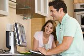 Couples In Kitchen With Computer And Coffee Smiling