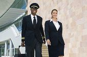 stock photo of cabin crew  - Airplane cabin crew walking together at the airport with bags - JPG