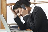 Side view of a tensed business woman communicating on cell phone