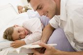 Man Reading Book To Young Girl In Bed Smiling