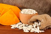 Pumpkin seeds in sack, on wooden background
