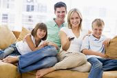 Famílias sentado na sala de estar com controle remoto sorrindo