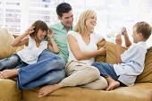 Families Sitting In Living Room With Digital Camera Smiling