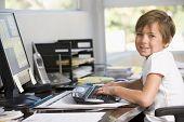Junge im home-Office mit Computer lächelnd