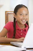 Junge Frau mit Laptop in Dining Room smiling