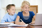 Two Young Children With Laptop Doing Homework In Dining Room Smiling
