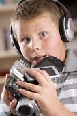 Young Boy Wearing Headphones In Bedroom Holding Many Electronic Devices
