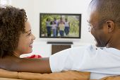 Couples In Living Room Watching Television Smiling