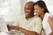 Couples In Living Room Using Laptop And Smiling
