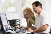 Couples In Home Office At Computer Frowning
