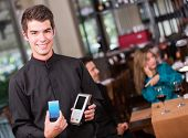 Waiter holding a dataphone at the restaurant
