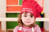 A little child wearing a chef hat