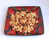 Mixed nuts on a black and red plate