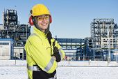 Industrial worker wearing all safety clothing necessary, such as hearing protection, a hard hat, chemical resistant reflective coat, gloves and safety glasses. Proudly smiling into the camera
