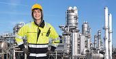 Proud and confident chemical engineer smiling into the camera in front of a petrochemical plabnt, wi