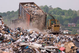image of bulldozers  - A bulldozer moving garbage on a landfill waste site as a garbage truck dumps more - JPG