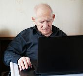 serious old man working on a computer