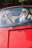 Mature couple in red cabriolet on sunny day smiling at camera