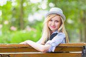 Sorrindo Hipster garota sentada no banco do Parque da cidade