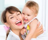 Mother and Baby kissing and hugging at Home. Happy Smiling Family Portrait. Mom and Her Child Having