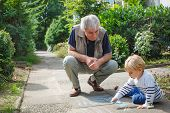 Little Blond Toddler Boy And Happy Grandfather Painting With Chalk Outdoors