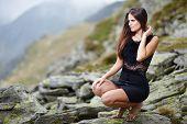Elegant Woman In Dress Sitting On The Rocks