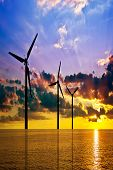 stock photo of wind-vane  - Wind power and colorful sunset over the sea - JPG