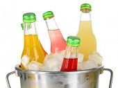Bottles with tasty drinks in bucket with ice cubes, isolated on white