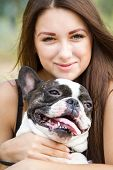 Smiling Young Girl Holding A Bulldog