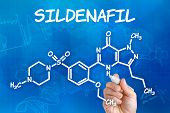 Hand with pen drawing the chemical formula of sildenafil
