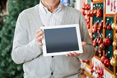 Midsection of senior man holding digital tablet at Christmas store