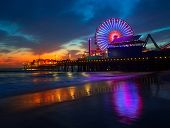 stock photo of nightfall  - Santa Monica California sunset on Pier Ferrys wheel and reflection on beach wet sand - JPG