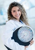 Female nutritionist with a weight scale at the hospital