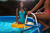 Two attractive slim and tanned young ladies with inflatable rings in swimming pool on vacation or holiday
