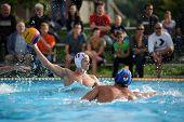 KAPOSVAR, HUNGARY - SEPTEMBER 15: Norbert Juhasz-Szelei (white) in action at a Hungarian championship waterpolo game between Kaposvar (white) vs Honved (blue) on September 15 2013 in Kaposvar, Hungary