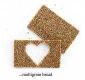 Two multigrain slices of bread with cut out shape of heart, isolated on white