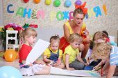 Five kids and holiday representative draw on floor at funny children party. Inscription Happy Birthday on wall.